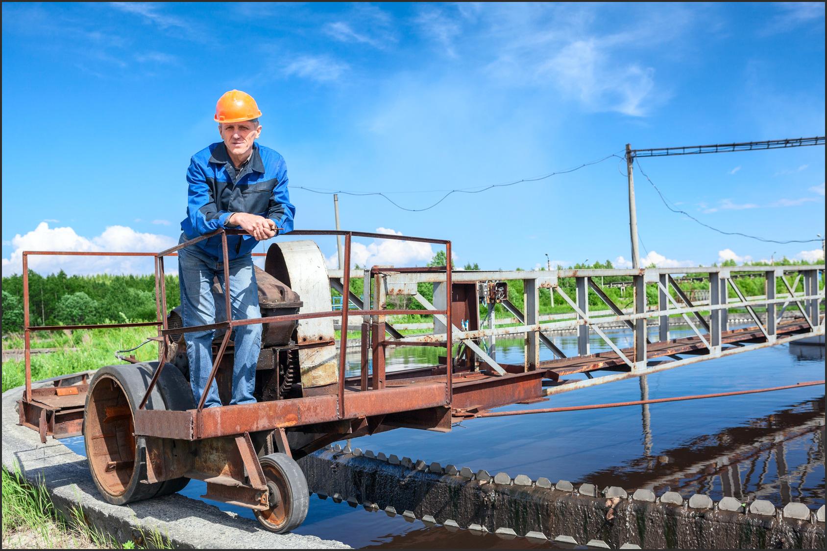 Industriearbeiter im Blaumann und gelbem Sicherheitshelm.